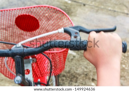 Hand on young child on the bicycle handlebar on concrete road - stock photo
