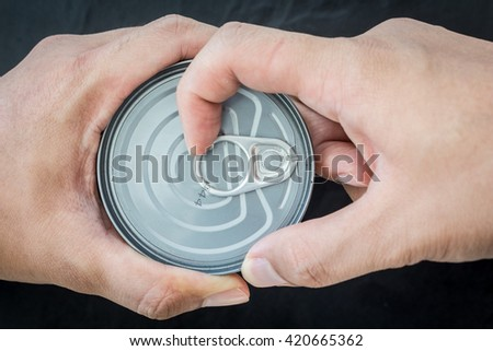 Hand open cans on black background - stock photo