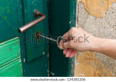 Hand open old door with old key - stock photo