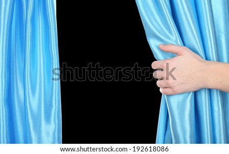 Hand opening curtain on black background - stock photo
