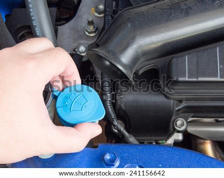 Hand opening the liquid cap in car engine - stock photo