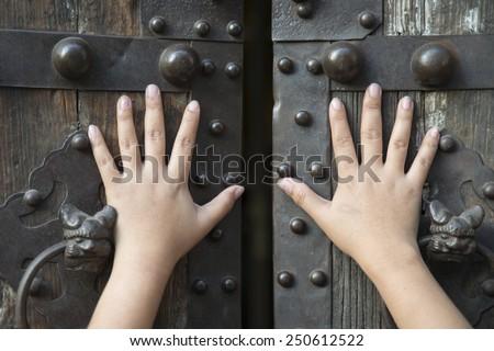 Hand opening the wooden door - stock photo