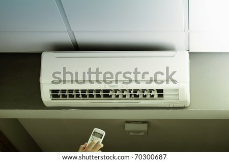 Hand operating remote controller of an air conditioner in modern office. - stock photo