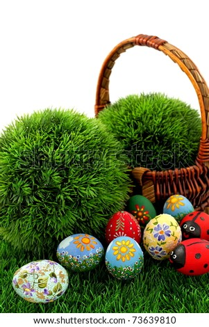 Hand painted beautiful  colorful  easter eggs in wicker basket on fresh green grass - stock photo