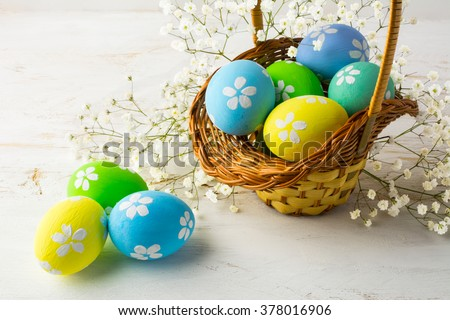 Hand-painted decorated Easter eggs in the basket with small white baby's breath flowers on a white wooden background, close up. Easter eggs. Easter. Easter background  - stock photo