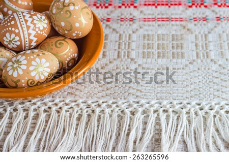 hand-painted Easter eggs in a plate on a tablecloth woven - stock photo