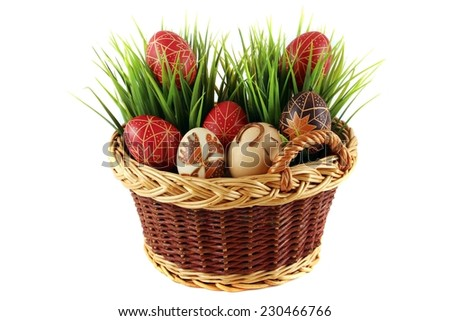 Hand-painted easter eggs in the wicker basket, white pattern, green grass - stock photo
