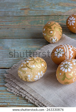 hand-painted Easter eggs on a cloth background on a wooden background - stock photo