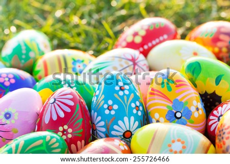 Hand-painted Easter eggs on grass. Floral, colorful spring patterns and designs. Traditional, artistic and unique. - stock photo