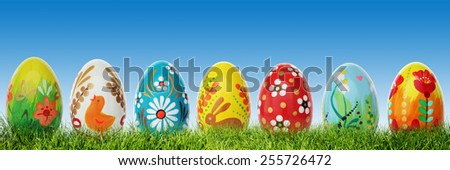 Hand painted Easter eggs on grass. Panorama, banner. Floral, colorful spring patterns and designs. Traditional, artistic and unique. - stock photo