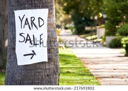 Hand painted paper yard sale sign with direction arrow stapled to a palm tree. - stock photo