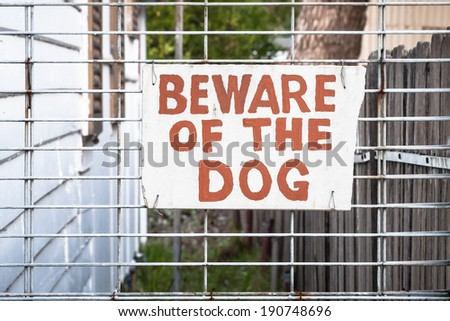 Hand painted red and cream sign wired onto a wire fence by the side of a house stating: BEWARE OF THE DOG - stock photo