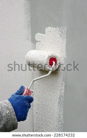 Hand painting a wall with a paint roller  - stock photo