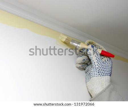 Hand painting a white wall - stock photo