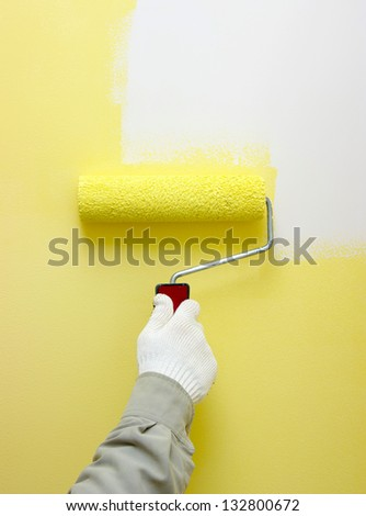 Hand painting a white wall with a paint roller - stock photo