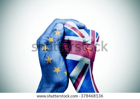 hand patterned with the flag of the European Community envelops another hand patterned with the flag of the United Kingdom - stock photo