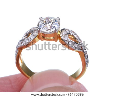 Hand pick golden ring with diamond isolated on white background. - stock photo
