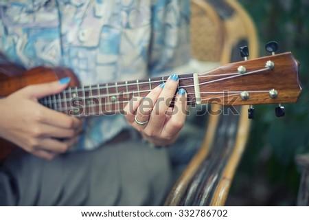 hand picking Guitar Ukulele vintage effect and soft focus. - stock photo