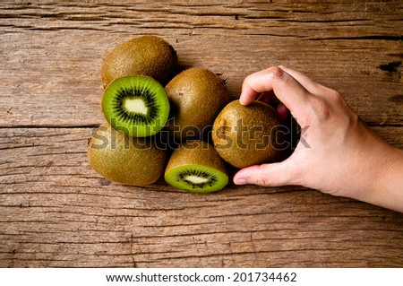 Hand Picking (Harvest,Show,Select,Hold,Choose) Fresh Group of Kiwi Fruits Sliced on Wood Table Background, Rustic Still Life Style.
