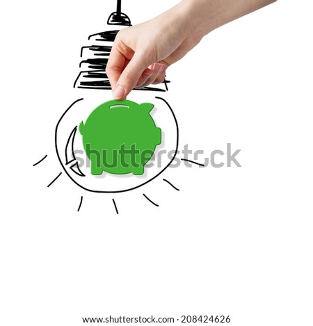 Hand picking paper piggy bank with bulb sketch in background - stock photo