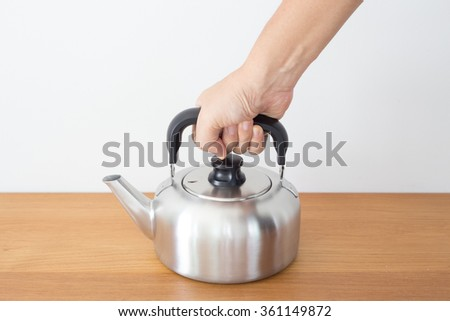 Hand picking stainless kettle on wood table with white background. - stock photo