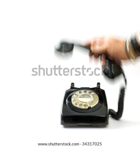 hand picking up receiver of black telephone; dynamic motion blur; excellent copy-space - stock photo
