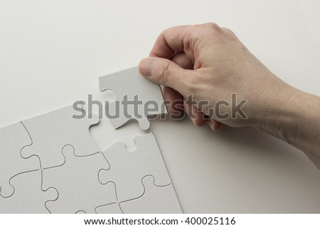 Hand places last puzzle piece in puzzle