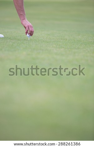 Hand placing ball on golf tee - stock photo
