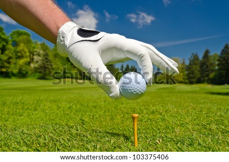 hand placing golf ball on tee over beautiful golf course with blue sky