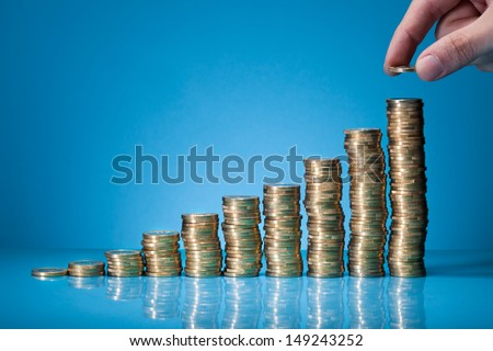 Hand Placing More Money To Growth Chart Of Coins - stock photo