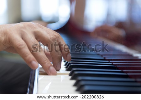 Hand Playing Classical Music with Piano Keys - stock photo