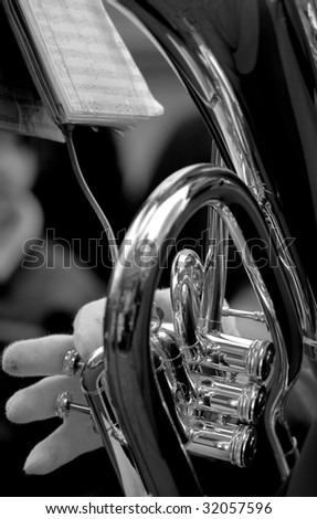 Hand playing the tuba in black and white - stock photo