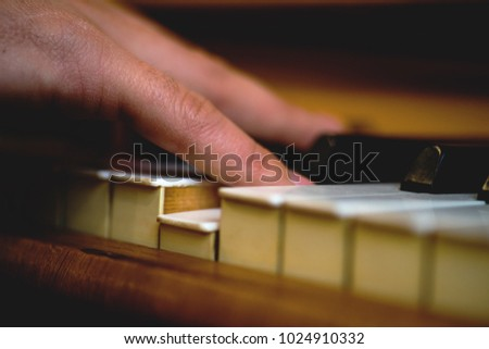 Hand playing upright piano, shallow depth of field shot with nice warm tone
