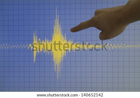 Hand pointing a yellow earthquake with a blue background and a grid - stock photo