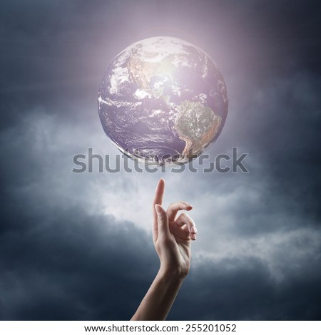 hand pointing at planet in space. Elements of this image are furnished by NASA