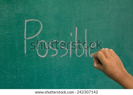 Hand pointing at possible word of success concept on chalkboard - stock photo