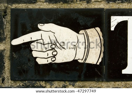 Hand pointing direction on street sign, London, England - stock photo