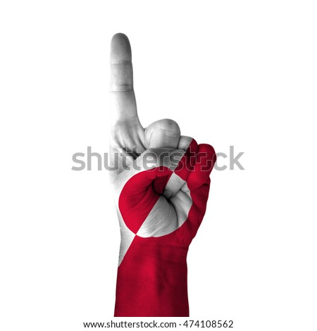 Hand pointing thumb up direction, greenland painted with flag as symbol of up direction, first and number one symbol - isolated on white background
