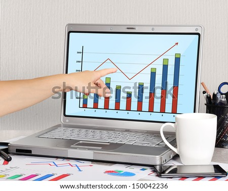 hand pointing to chart on screen laptop - stock photo
