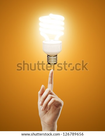 hand pointing to energy saving lamp on yellow background