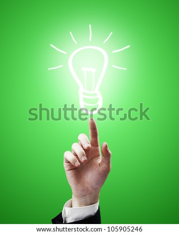 hand points to a drawing of  lamp on green background - stock photo