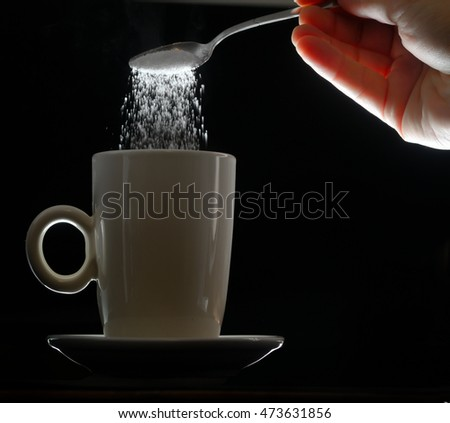 hand pouring brown sugar in white cup of coffee