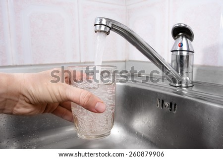 hand pours water into a glass - stock photo