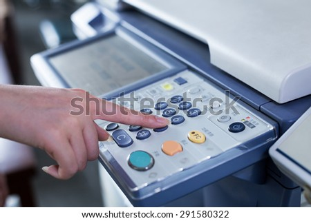 hand press button on panel of printer - stock photo