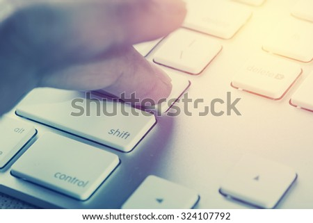 Hand press ENTER to computer keyboard. Vintage filter - stock photo
