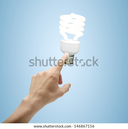hand presses energy saving lamp on a blue background