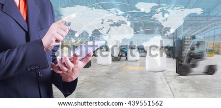 hand presses on world map with digital tablet,warehouse worker loading goods by forklift  for Logistic Import Export background (Elements of this image furnished by NASA) - stock photo
