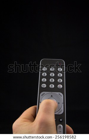 Hand pressing a button on a remote controll - stock photo