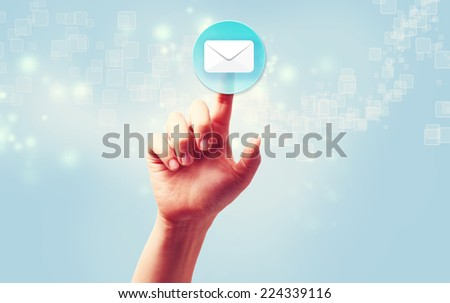 Hand pressing a envelope icon over light blue background - stock photo