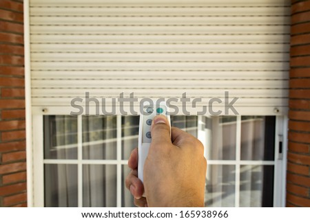 hand pressing a remote control controlling an electric roller shutter - stock photo
